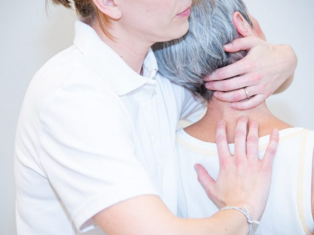 Physiotherapie - Frau wird am Nacken behandelt