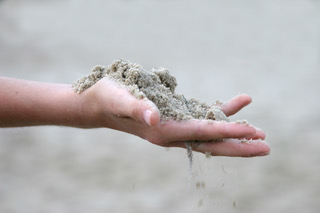 Hand hält Sand